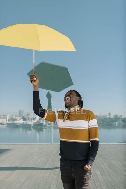 Посмішка людини з рукою в кишені, тримаючи жовту парасольку, стоячи проти скляної стіни. — стокове фото