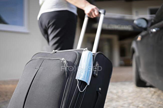 Turista puxando bagagem com rodas enquanto caminha em direção ao hotel durante coronavírus — Fotografia de Stock