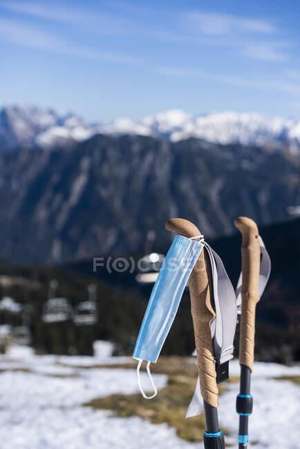 Máscara protetora pendurada no bastão de esqui contra montanhas — Fotografia de Stock