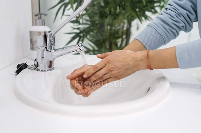 Enfermera lavándose las manos en el lavabo en la clínica - foto de stock