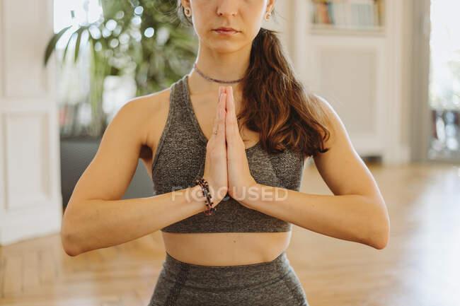 Женщина медитирует с сжатыми руками дома — стоковое фото