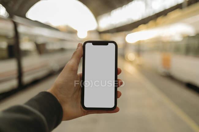 Joven usando teléfono con pantalla en blanco en la estación de tren - foto de stock