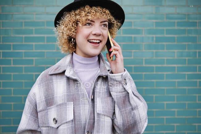 Donna sorridente guardando altrove mentre parla sul telefono cellulare contro il muro blu — Foto stock