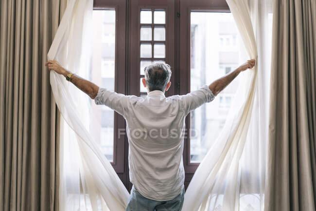 Uomo tende di apertura in camera d'albergo — Foto stock