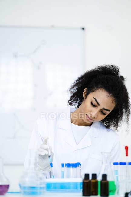 Jeune chercheur injectant du liquide dans une éprouvette en laboratoire — Photo de stock