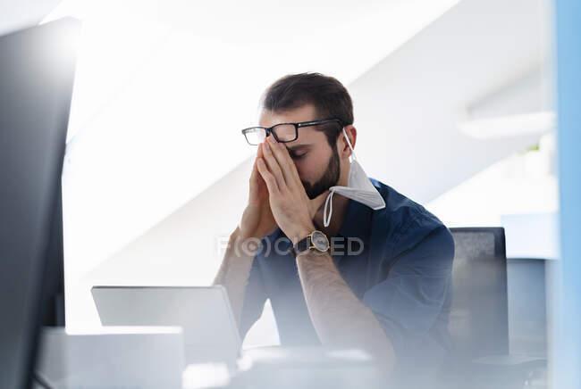 Joven emprendedor con mascarilla protectora sentado con la cabeza en las manos en la oficina - foto de stock