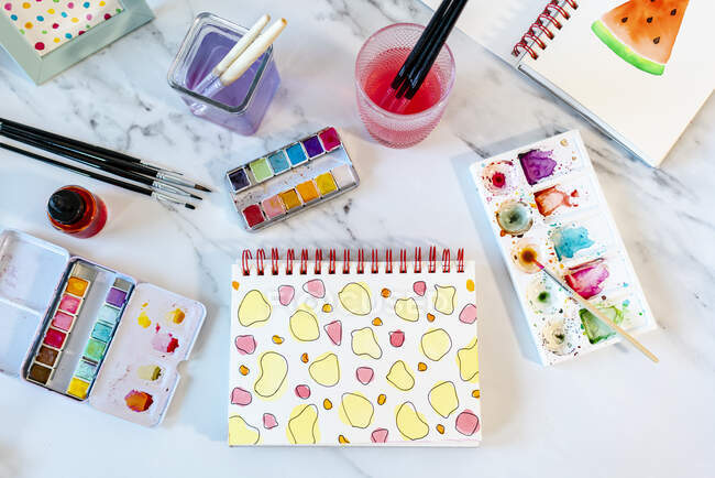 Abstract water color painting with equipment on marble table — Stock Photo
