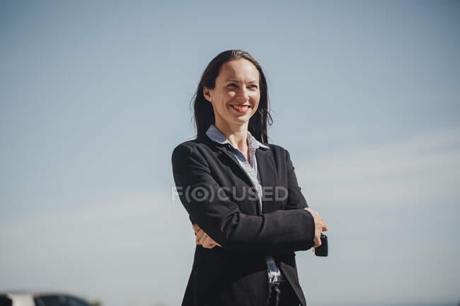 Profesional femenino confiado sonriendo mientras está de pie con los brazos extendidos contra el cielo - foto de stock