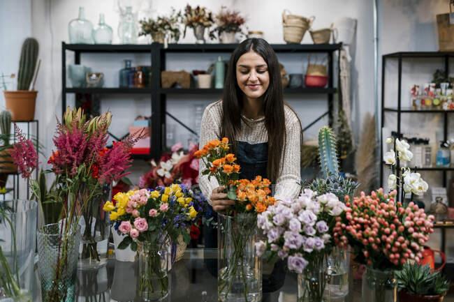 Молодая девушка-флористка устраивает цветы в магазине — стоковое фото