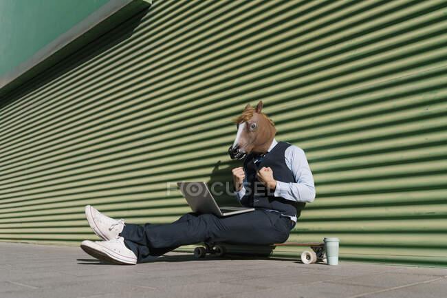 Бізнесмен у конячій масці з жестом ноутбука під час сидіння біля зеленої стіни. — стокове фото