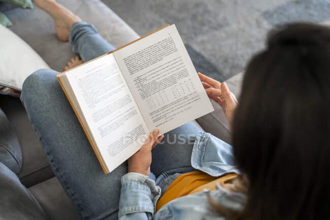 Женщина читает книгу, расслабляясь дома на диване — стоковое фото