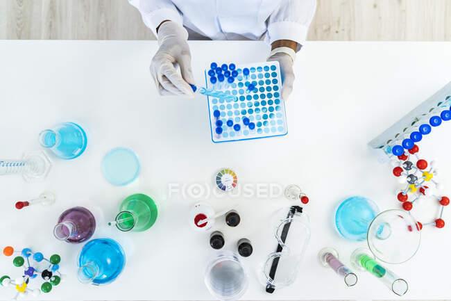 Жіночий дослідник видаляє тестову трубку з мікроплит на столі в лабораторії. — стокове фото