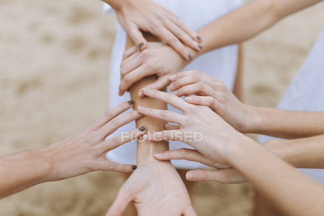 Female friends touching and holding hands on sand — Stock Photo