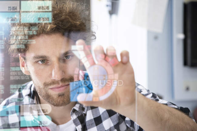 Young male entrepreneur touching projection screen in factory — Stock Photo