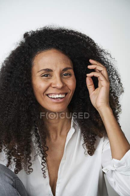Щаслива жінка з волоссям над сірим фоном — стокове фото