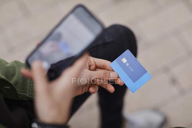 Hombre tomando fotos de la tarjeta de crédito a través del teléfono móvil - foto de stock