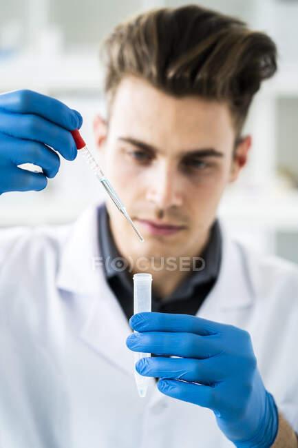Científico masculino sosteniendo tubo de ensayo y pipeta mientras que hace la sustancia química en laboratorio - foto de stock