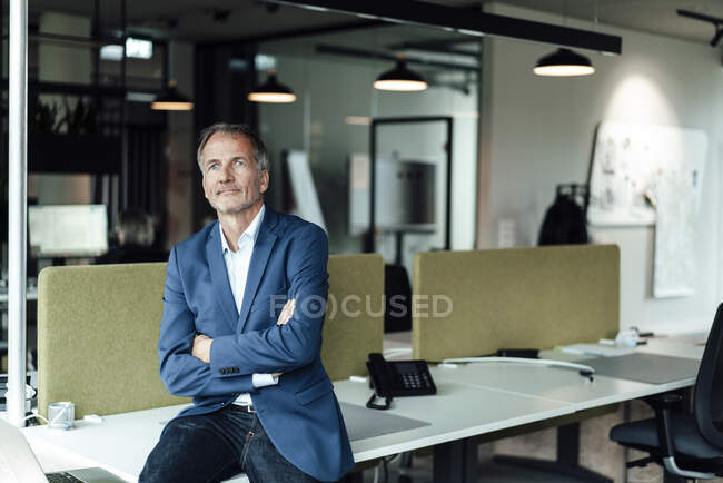 Male business professional with arms crossed sitting on desk in office — Stock Photo