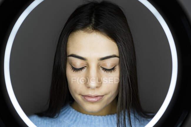 Молодая женщина стоящая с закрытыми глазами перед вспышкой фотоаппарата — стоковое фото