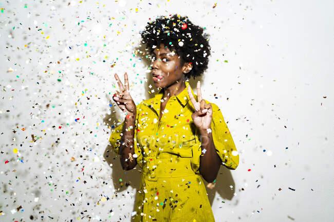 Donna che mostra segno di pace e sporgere la lingua mentre in piedi in mezzo a coriandoli sullo sfondo bianco — Foto stock