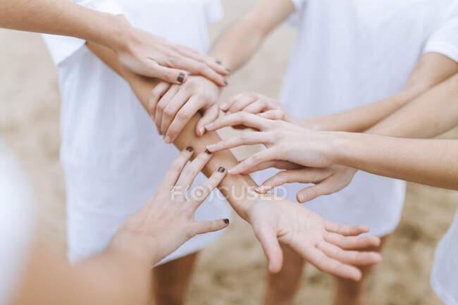 Amigas tocando manos en la arena - foto de stock