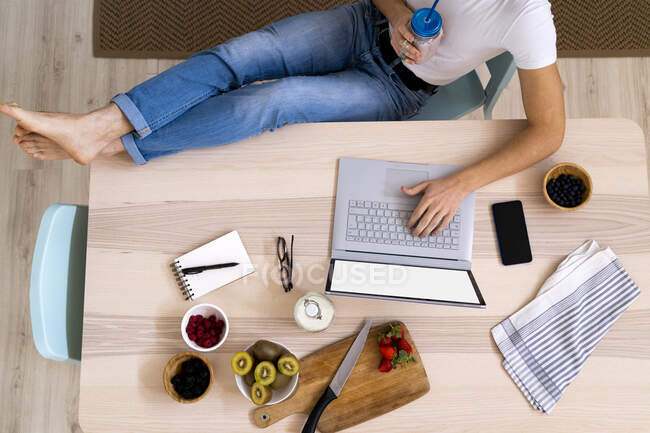 Man holding smoothie jar while using laptop sitting at table in kitchen — Stock Photo