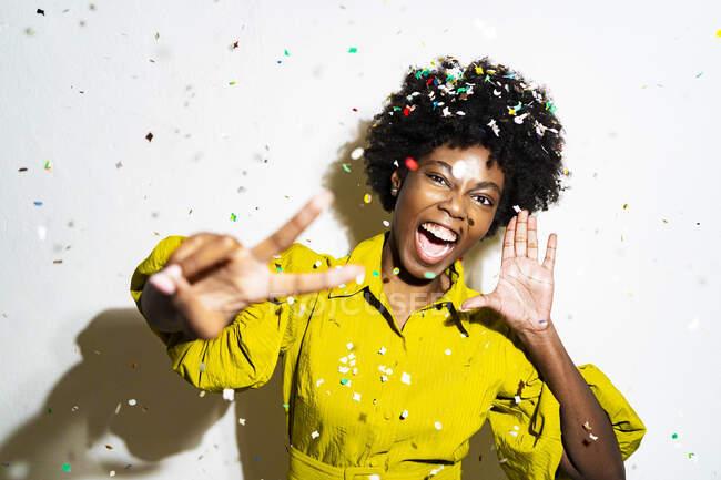 Confetti cadere sulla donna gesticolando segno di pace mentre in piedi sfondo bianco — Foto stock