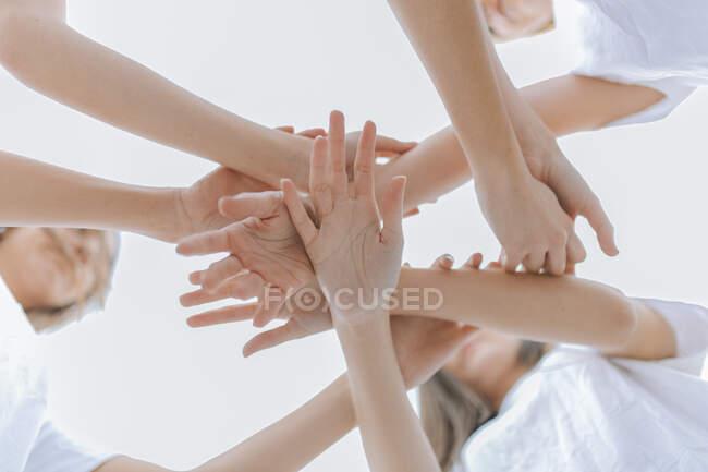 Amigas con manos apiladas - foto de stock