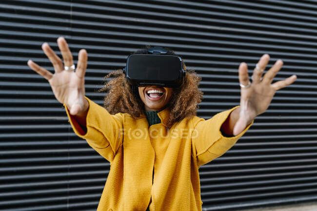 Cheerful woman watching video through wearable computer against wall — Stock Photo