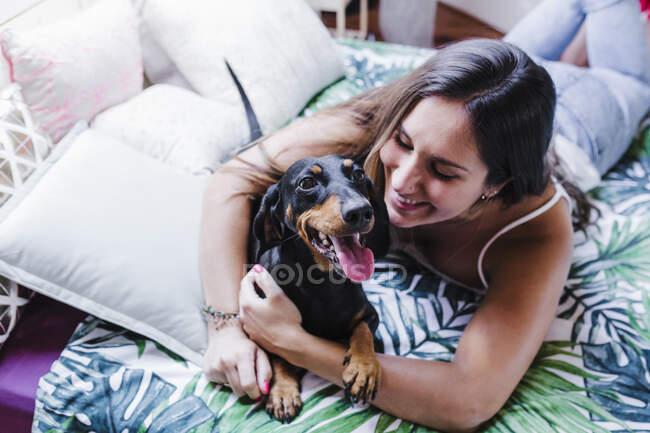 Mujer sonriente abrazando al perro mientras está acostado en la cama en casa - foto de stock