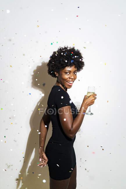 Confetti cadere sulla donna allegra tenendo flauto champagne mentre in piedi contro sfondo bianco — Foto stock