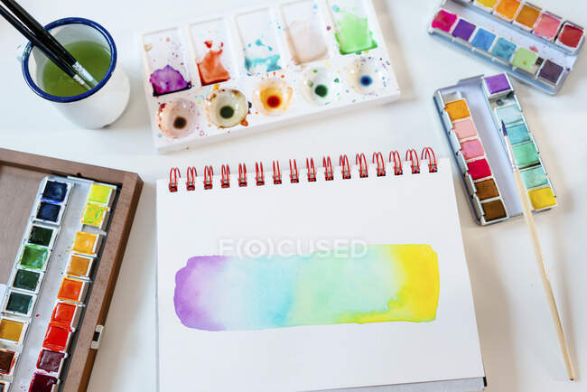 Abstract of rainbow water color painting with equipment on table — Stock Photo