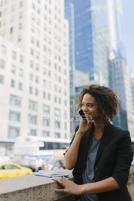 Afro feminino profissional falando no telefone inteligente perto de edifícios de escritório na cidade — Fotografia de Stock