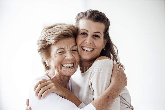 Весела старша жінка, яка обіймає усмішку онуки. — стокове фото