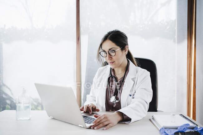 Experiencia médica femenina utilizando el ordenador portátil mientras está sentado contra la ventana en el hospital - foto de stock