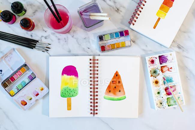 Barra de sorvete e fatia de melancia pintada em livro sobre mesa de mármore — Fotografia de Stock