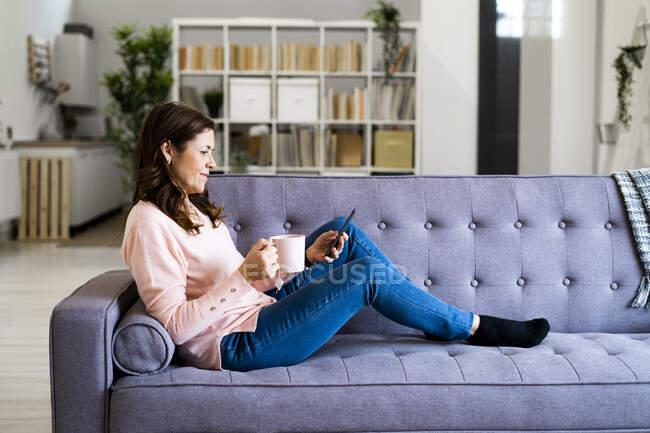 Женщина с чашкой кофе с помощью мобильного телефона, сидя на диване дома — стоковое фото