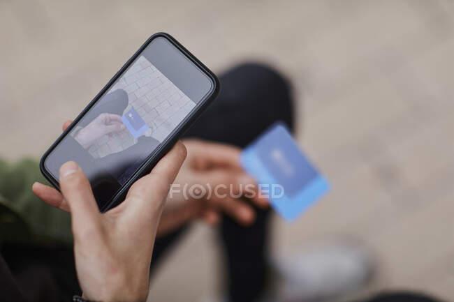 Hombre tomando fotos de la tarjeta de crédito a través del teléfono inteligente - foto de stock