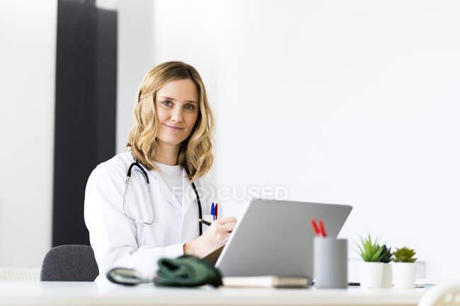 Sonriente doctora escribiendo en el portapapeles mientras está sentada en el escritorio - foto de stock