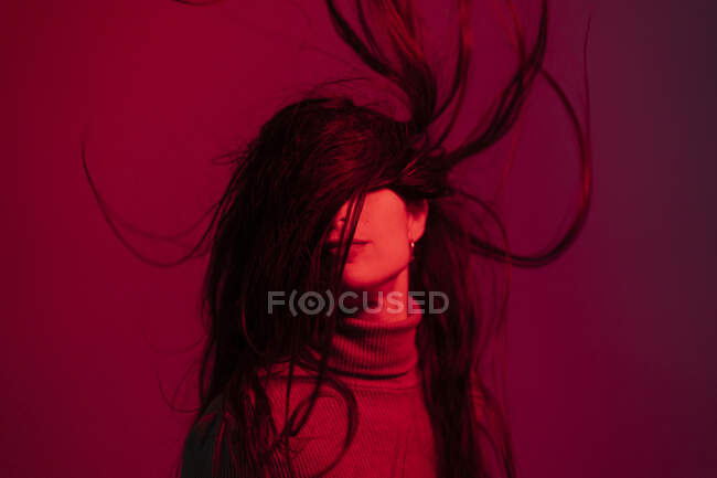 Woman tossing hair against red background — Stock Photo
