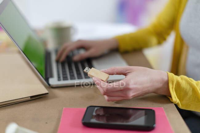 Женщина держит карту USB на ноутбуке и мобильный телефон на столе дома — стоковое фото