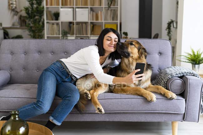 Sonriente joven mujer tomando selfie con perro en sala de estar - foto de stock