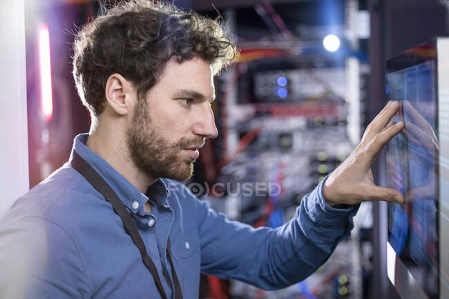 Чоловік ІТ - технік дивиться на екран комп