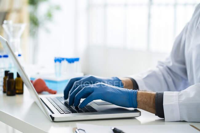Cientista do sexo masculino trabalhando no laptop em laboratório — Fotografia de Stock