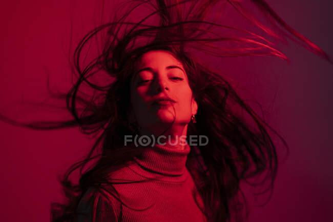Mujer lanzando el pelo largo sobre fondo rojo - foto de stock