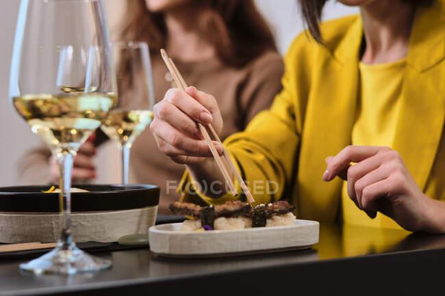 Mujer comiendo sushi fresco con palillos mientras está sentada por una amiga en el restaurante - foto de stock