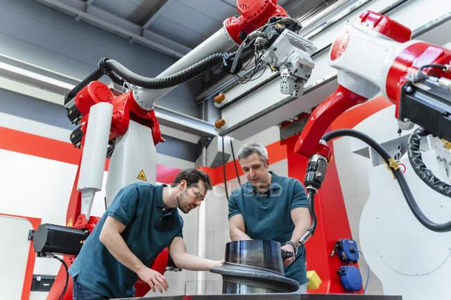 Чоловічі зварники працюють на автоматизованій машині на заводі. — стокове фото