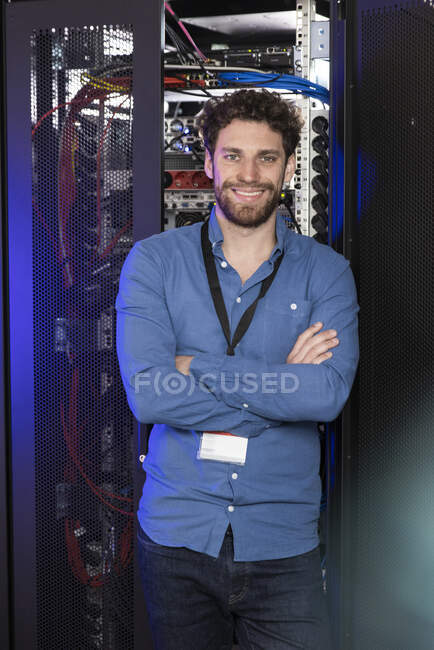 Smiling IT specialist with arms crossed standing in data center — Stock Photo
