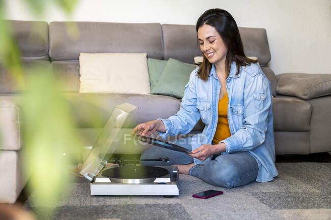 Lächelnde Frau mit Plattenspieler hält Rekord, während sie zu Hause auf dem Sofa sitzt — Stockfoto