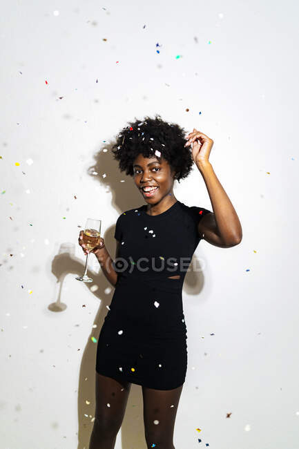 Confetti cadere su donna felice ballare con champagne flauto mentre in piedi su sfondo bianco — Foto stock